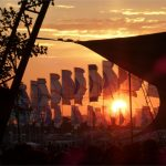 Sunset through The Glade stage and Other Stage flags